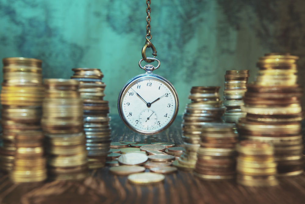 Time is money :Old coins and clock.